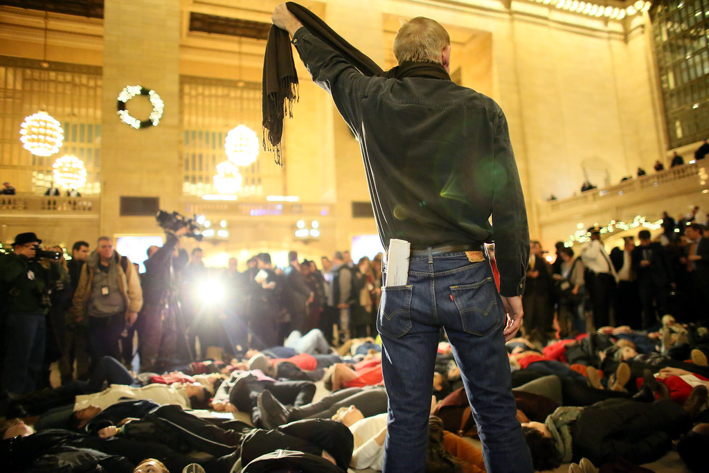 . NEW YORK - DECEMBER 3: A man symbolically chokes himself with a scarf during a protest in Grand Central Terminal December 3, 2014 in New York. Protests began after a Grand Jury decided to not indict officer Daniel Pantaleo. Eric Garner died after being put in a chokehold by Pantaleo on July 17, 2014. Pantaleo had suspected Garner of selling untaxed cigarettes. (Photo by Yana Paskova/Getty Images)