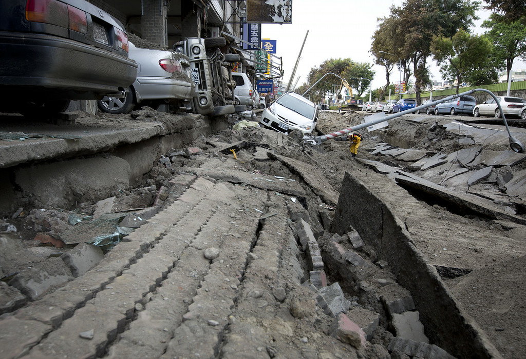 . Vehicles lie on the damaged road after gas explosions in southern Kaohsiung on August 1, 2014 in Kaohsiung, Taiwan. A series of powerful gas blasts killed 25 people and injured up to 267 in the southern Taiwanese city of Kaohsiung, overturning cars and ripping up roads, officials said.  (Photo by Ashley Pon/Getty Images)