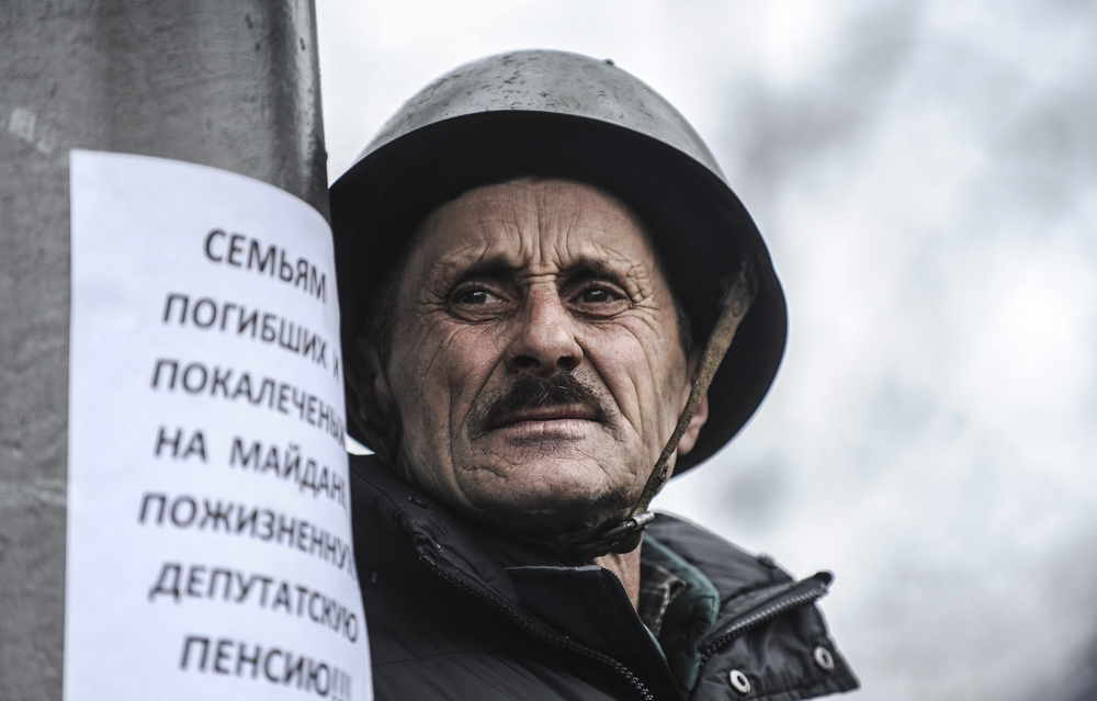 ". An anti-government protester waits outside the parliament building in Kiev on February 22, 2014. Ukraine\'s parliament on February 22 voted to hold early presidential elections on May 25, passing a resolution stating that Viktor Yanukovych had failed to properly fulfil his duties as president. The resolution said that Yanukovych ""is removing himself (from power) because he is not fulfilling his obligations, and (that parliament) is setting elections for May 25.\"" (BULENT KILIC/AFP/Getty Images)"