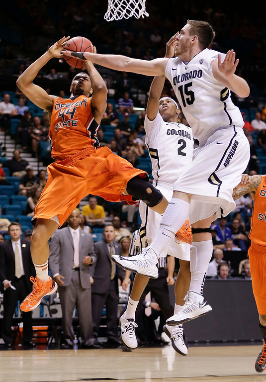 . Oregon State\'s Devon Collier (44) shoots against Colorado\'s Xavier Johnson (2) and Shane Harris-Tunks in the first half of a Pac-12 tournament NCAA college basketball game, Wednesday, March 13, 2013, in Las Vegas. (AP Photo/Julie Jacobson)
