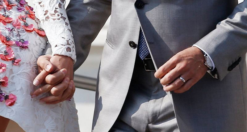 . George Clooney, right, wearing the ring, is flanked by his wife Amal Alamuddin as they leave the Aman luxury Hotel in Venice, Italy, Sunday, Sept. 28, 2014. George Clooney married human rights lawyer Amal Alamuddin Saturday, the actor\'s representative said, out of sight of pursuing paparazzi and adoring crowds. (AP Photo/Luca Bruno)