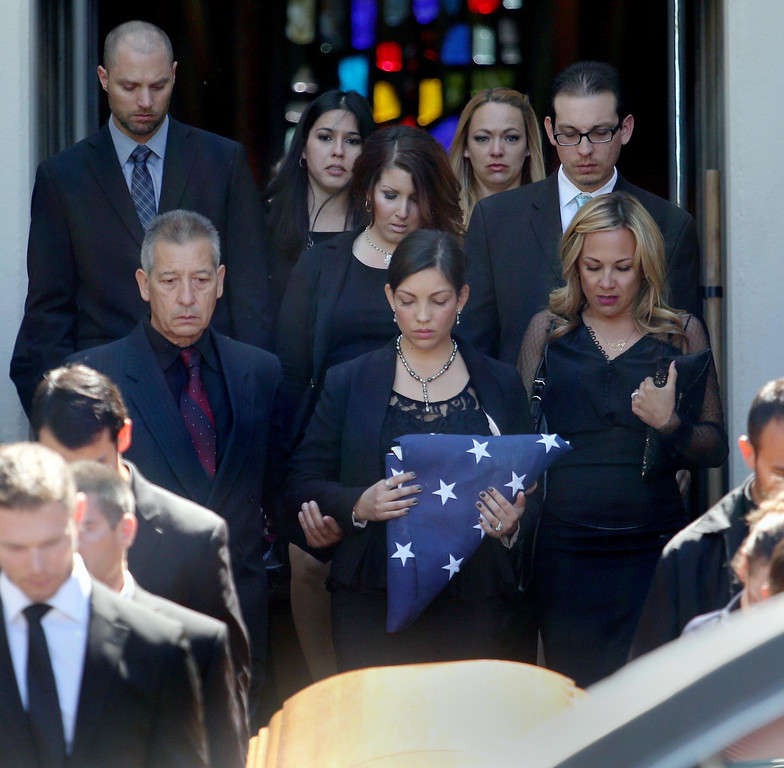 . Elizabeth Huerta Boyer, center, is joined by family and friends as she carries a flag as she follows the casket of her husband Quinn Boyer, 34, of Dublin, out of St. Theresa Catholic Church in Oakland, Calif., on Tuesday, April 16, 2013.  (Jane Tyska/Staff)