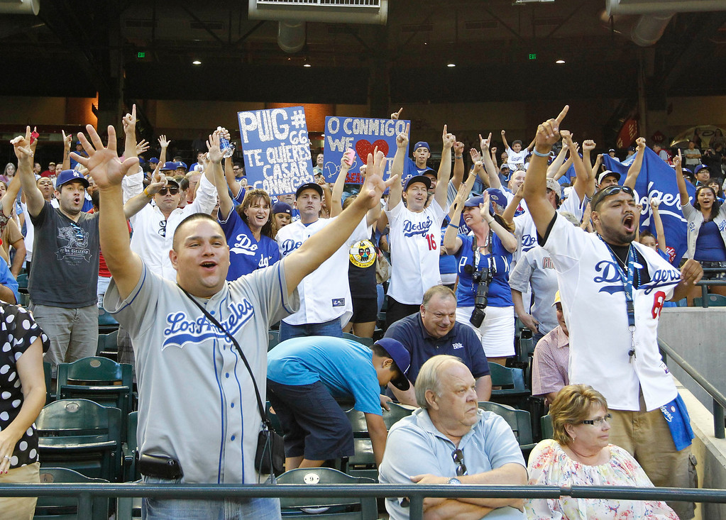 . Los Angeles Dodgers fans celebrate their win over the Arizona Diamondbacks after a baseball game, Thursday, Sept. 19, 2013, in Phoenix. The Dodgers clinched the N.L. West with their 7-6 win over the Diamondbacks.  (AP Photo/Matt York)
