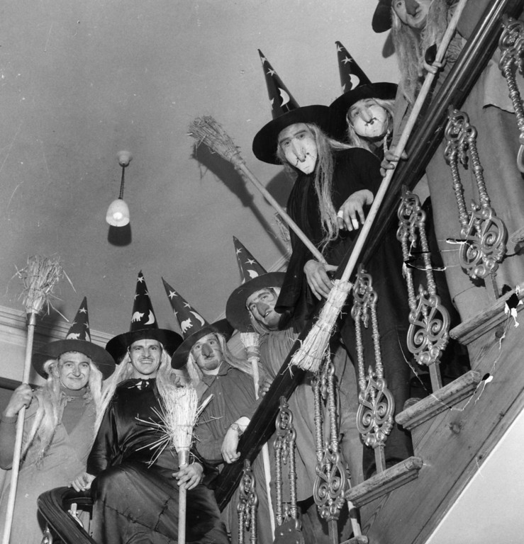 . circa 1950:  A group of men in costume as witches, complete with brooms, to celebrate Halloween, line the staircase of a house.  (Photo by George Pickow/Three Lions/Getty Images)