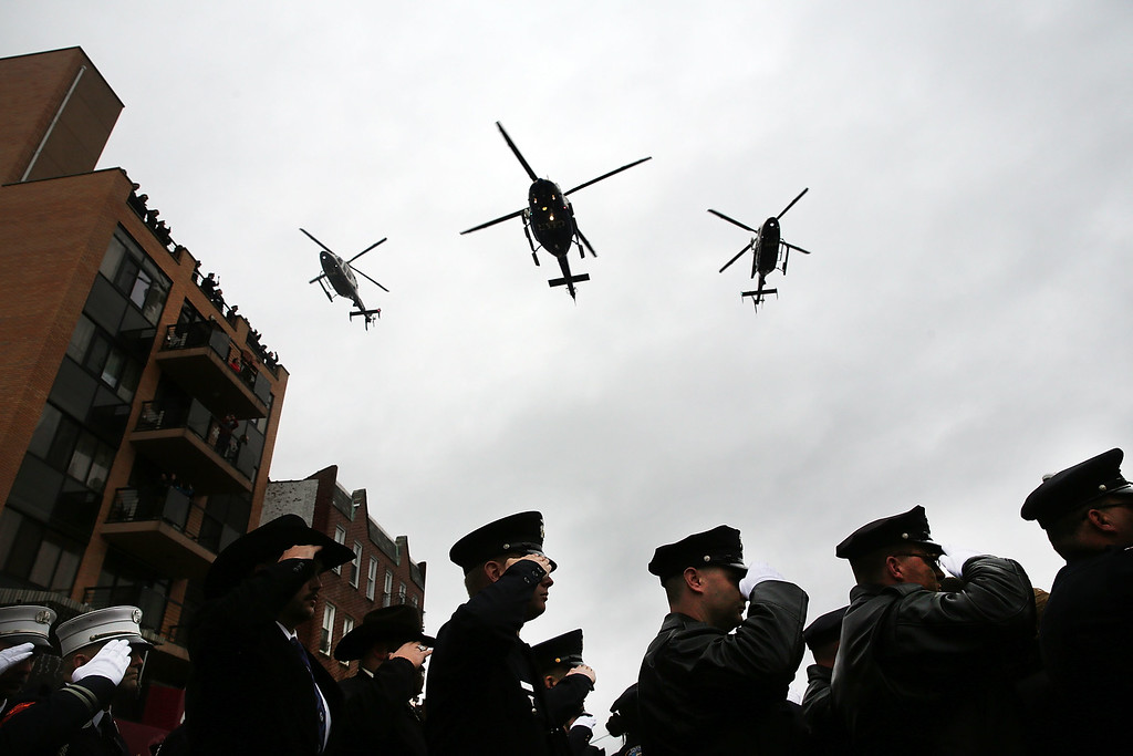 . Police helicopters do a fly over at the conclusion of the funeral service for slain New York City Police Officer Wenjian Liu January 4, 2015 in New York City. Officers Wenjian Liu and Rafael Ramos were killed in an ambush while sitting in their patrol car last month on December 20. Thousands of fellow officers, family, friends and current FBI director is James Comey are expected at the Brooklyn funeral home for the service. Officer Ramos, was buried last week in Queens. (Photo by Spencer Platt/Getty Images)