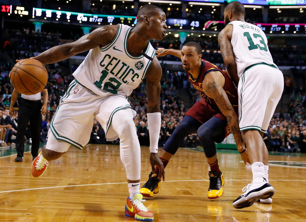 . Boston Celtics guard Terry Rozier (12) makes a dribble move as Cleveland Cavaliers guard George Hill (3) tries to get through a pick set by Celtics forward Marcus Morris (13) during the third quarter of Game 1 of the NBA basketball Eastern Conference Finals, Sunday, May 13, 2018, in Boston. (AP Photo/Michael Dwyer)