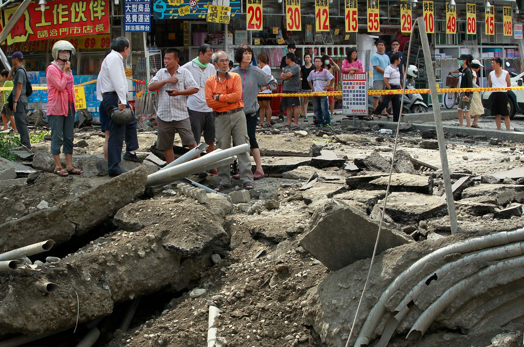 . Locals survey the damage from a massive gas explosion in Kaohsiung, Taiwan, Friday, Aug. 1, 2014. Scores of people were killed and more than 200 others injured when several underground gas explosions ripped through Taiwan\'s second-largest city overnight, hurling concrete through the air and blasting long trenches in the streets, authorities said Friday. (AP Photo/Wally Santana)