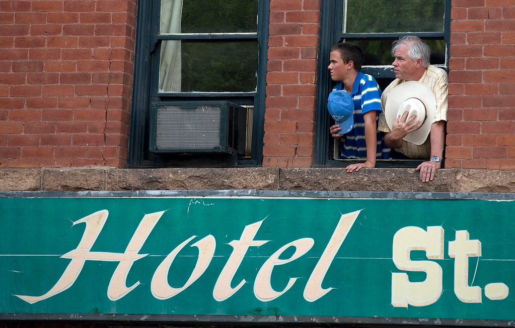 . A man and a teenage boy lean out the window of the Hotel St. Michael with their hats pulled over their hearts watching, Sunday, July 7, 2013 in downtown Prescott, Ariz., as 19 hearses slowly roll by carrying the 19 Granite Mountain Hotshot firefighters killed a week ago by an out-of-control blaze near Yarnell, Ariz. The nearly five-hour-long procession began near the state Capitol in Phoenix, went through the town where the Granite Mountain Hotshots were killed and ended in the mountain community of Prescott, where they lived and will be laid to rest this week.  (AP Photo/Julie Jacobson)