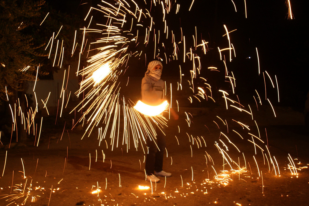 . A Palestinian youth plays with fireworks while Palestinian Authority President Mahmoud Abbas speaks to the United Nations General Assembly at the UN headquarters in New York, before the body votes on a resolution to upgrade the status of the Palestinian Authority to a nonmember observer state, in the West Bank city of Nablus, Thursday, Nov. 29, 2012. The Palestinians are certain to win U.N. recognition as a state on Thursday but success could exact a high price: delaying an independent state of Palestine because of Israel\'s vehement opposition.(AP Photo/Nasser Ishtayeh)