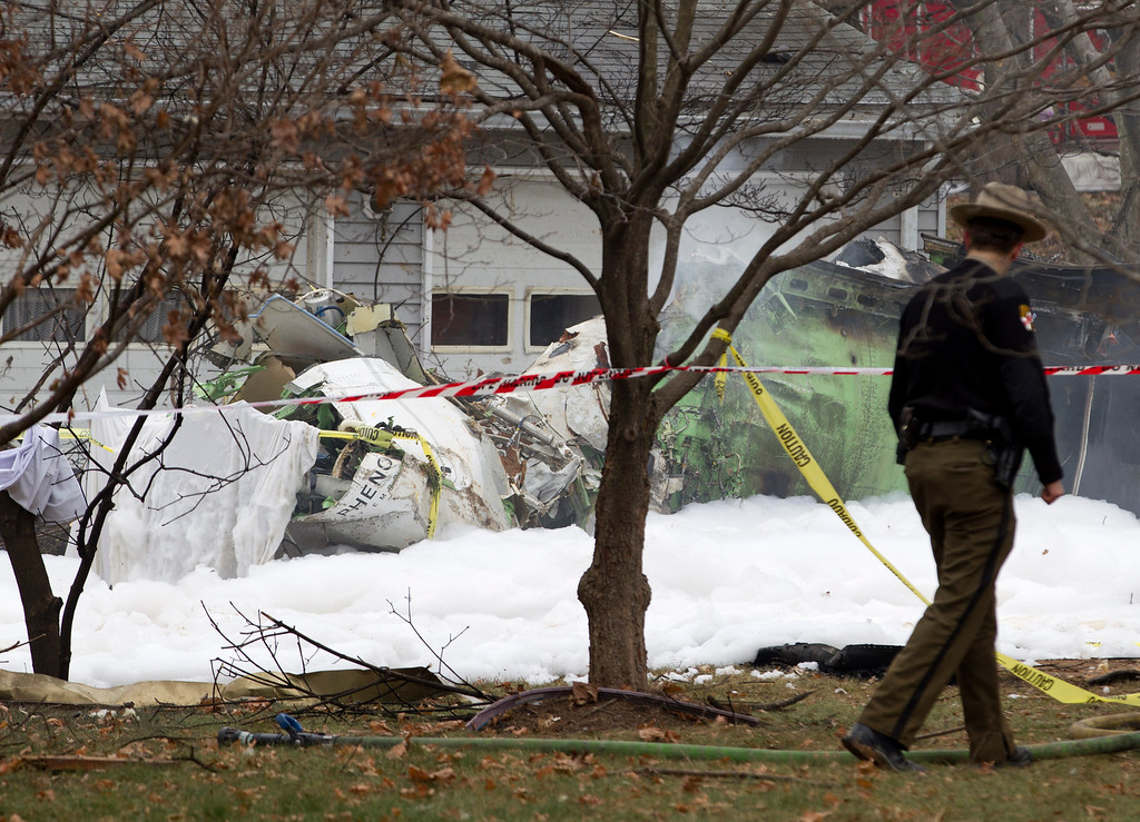. The wreckage of a small plane smolders in a house driveway after crashing in Gaithersburg, Md., Monday Dec. 8, 2014. The small, private jet has crashed into a house in Maryland\'s Montgomery County, and a fire official says at least three people on board were killed. (AP Photo/Jose Luis Magana)