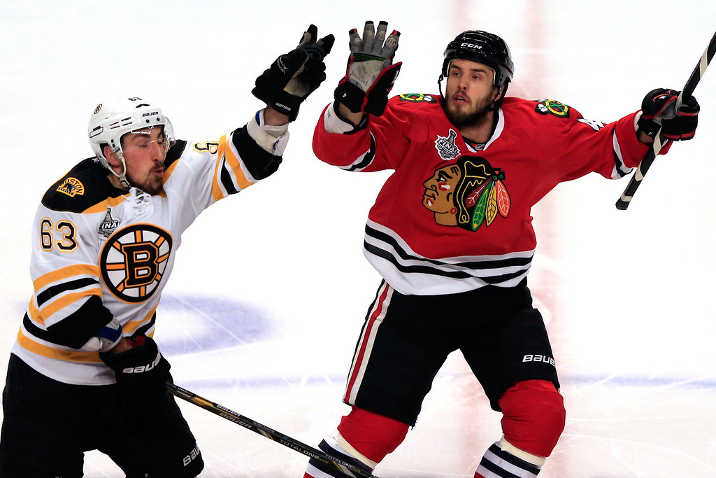 . CHICAGO, IL - JUNE 22:  Brad Marchand #63 of the Boston Bruins catches a puck out of the air against Niklas Hjalmarsson #4 of the Chicago Blackhawks in Game Five of the 2013 NHL Stanley Cup Final at United Center on June 22, 2013 in Chicago, Illinois.  (Photo by Jamie Squire/Getty Images)