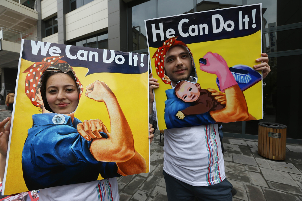 ". A couple pose for a picture parodying the ""We can do it\"" American propaganda poster during a march in central Ankara as part of the \""International Women\'s Day\"", on March 8, 2014. The \""International Women\'s Day\"" dates back to the beginning of the 20th Century and has been observed by the United Nations since 1975. (ADEM ALTAN/AFP/Getty Images)"
