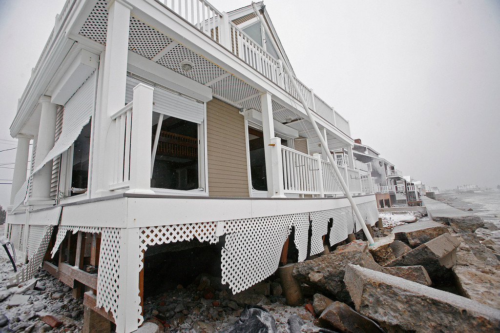 . A damaged house sits along the coast in the Brant Rock section of Marshfield, Mass., during a winter snowstorm Tuesday, Jan. 27, 2015. A storm packing blizzard conditions spun up the East Coast early Tuesday, pounding parts of coastal New Jersey northward through Maine with high winds and heavy snow. (AP Photo/The Quincy Patriot Ledger, Greg Derr)