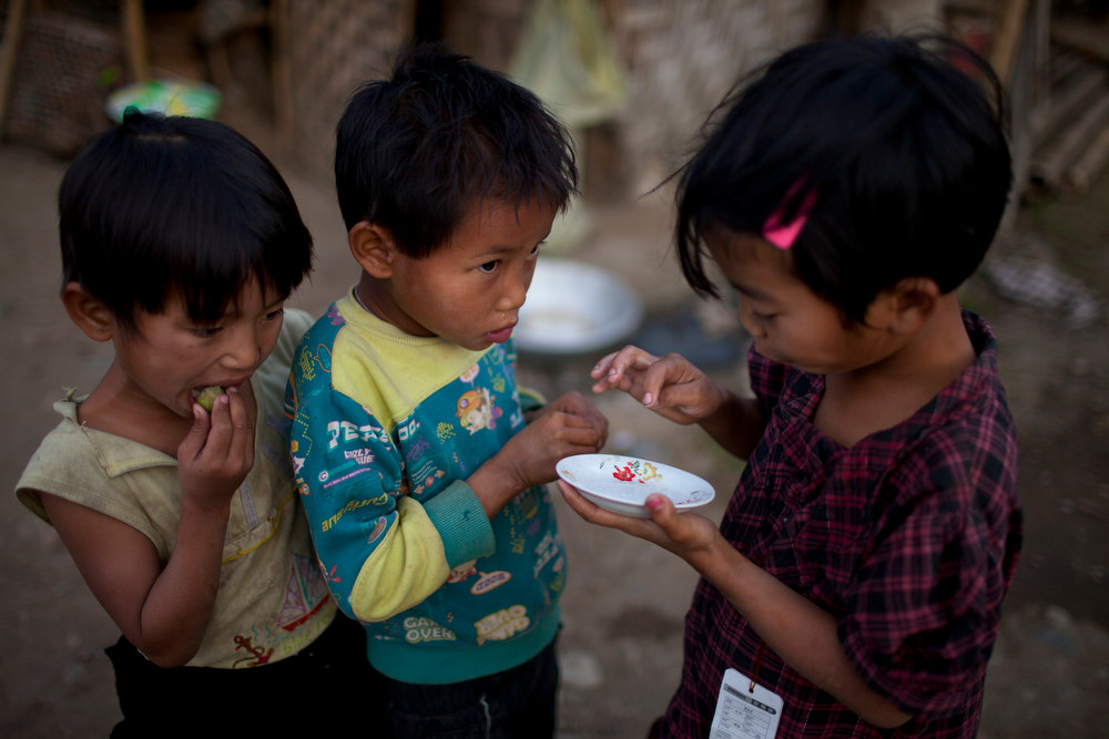 . Children eat dates after dipping them in a small plate with salt at an Internally Displaced Persons refuge camp set up at a land of Woichyai Baptist Church in the town of Laiza, in northern Myanmar\'s Kachin-controled region, Tuesday, Jan. 29, 2013. (AP Photo/Alexander F. Yuan)