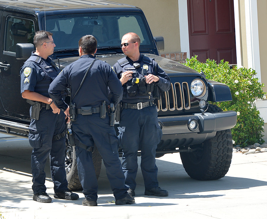 . Brentwood police officers keep watch in front of the home of  Sgt. Scott Lunger of the Hayward Police Department, who was shot and killed early Wednesday morning after making a traffic stop on a driver who was driving erratically in Hayward, as friends or family arrive at the home in Brentwood, Calif., on Wednesday, July 22, 2015. (Dan Rosenstrauch/Bay Area News Group)