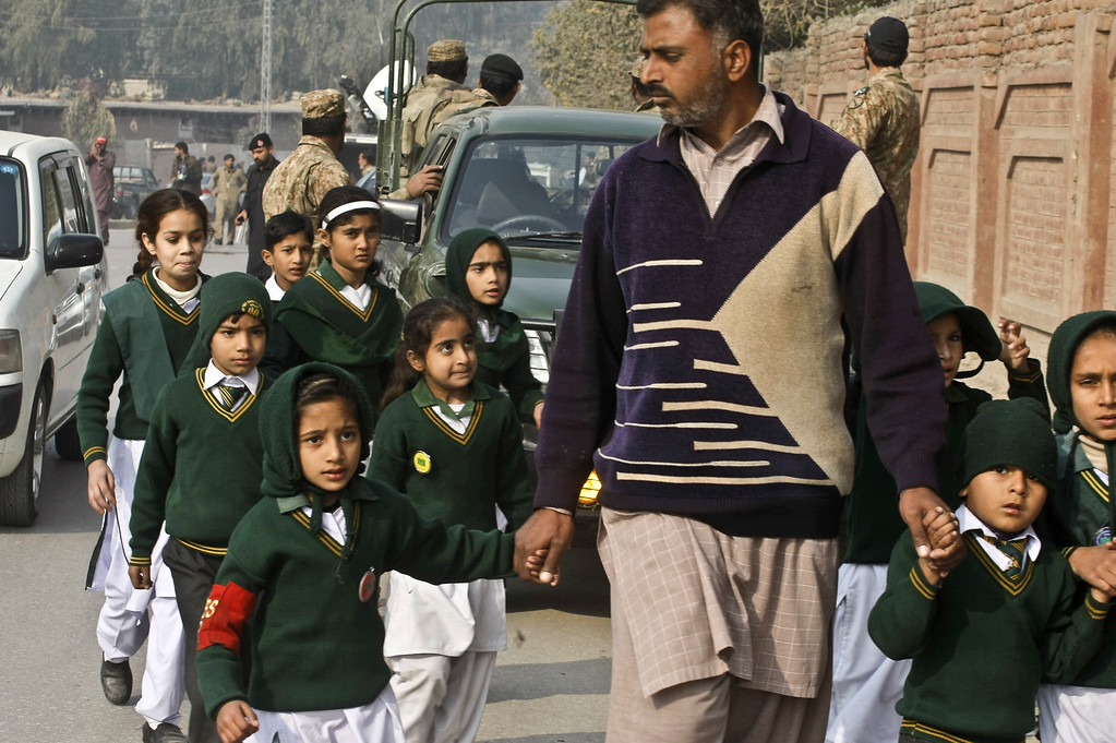 . A plainclothes security officer escorts students evacuated from a school as Taliban fighters attack another school nearby in Peshawar, Pakistan, Tuesday, Dec. 16, 2014. Taliban gunmen stormed a military-run school in the northwestern Pakistani city, killing and wounding scores, officials said, in the worst attack to hit the country in over a year. (AP Photo/Mohammad Sajjad)