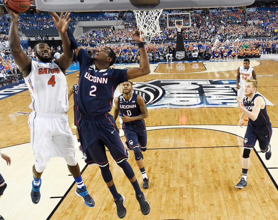 . CORRECTS LOCATION TO ARLINGTON, INSTEAD OF DALLAS - Florida center Patric Young (4) drives to the basket past Connecticut forward DeAndre Daniels (2) during the first half of the NCAA Final Four tournament college basketball semifinal, Saturday, April 5, 2014, in Arlington, Texas. (AP Photo/Chris Steppig, Pool)