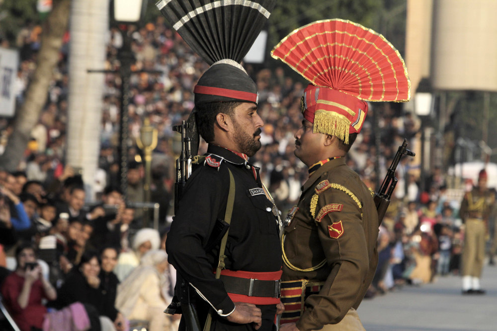 Description of . A Pakistani Ranger in black uniform and his Indian counterpart, march during a flag off ceremony, at the joint Pakistan-India border check post of Wagah near Lahore, Pakistan, Friday, Jan. 11, 2013. Pakistan has summoned India\'s top diplomat in the country to protest a pair of clashes along the disputed Kashmir border in the past week that killed two Pakistani soldiers. (AP Photo/K.M. Chaudary)