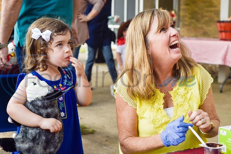 Natalie Ellis, 2, eats a marshmallow as DeeDee Keener laughs and chats with a parent during the Kids Kaleidoscope Preschool Toddler Fair at Pollard United Methodist Church in Tyler, Texas, on Thursday, Oct. 4, 2018. (Chelsea Purgahn/Tyler Morning Telegraph)