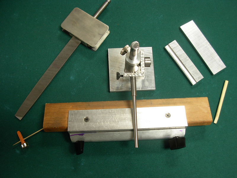 """The complete assembly, from bottom left moving clockwise is the magnetic toothpick, it is used to determine previously filed angles greater than 90 degrees. The file/hone component device is an assembly with a  """"credit card"""" diamond hone on one side and a steel plate on the other, for attaching lapping paper. They are used for honing or lapping the burnisher edge following the filing operation. The design is such that the angle for lapping either with the diamond card or paper is the same angle that was applied with the file. Next is the post assembly which is the heart of the system. It has an """"L"""" bracket that receives the tooling and is attached to a vertical post enabling the attached tooling to be positioned at variable or locked heights. The right side has a graduated scale for indicating the angular position of the """"L"""" bracket.  The two plates are used for setting the blade height before starting a filing operation, the other plate is used to establish proper height of the temporary vise jaws when using the post assembly on your wood working vise.The blond stick is a piece of bamboo which makes an excellent file cleaner for a mill bastard file. In front of the post assembly is a portable vise that can be clamped to any flat surface when using the device away from the workbench."""