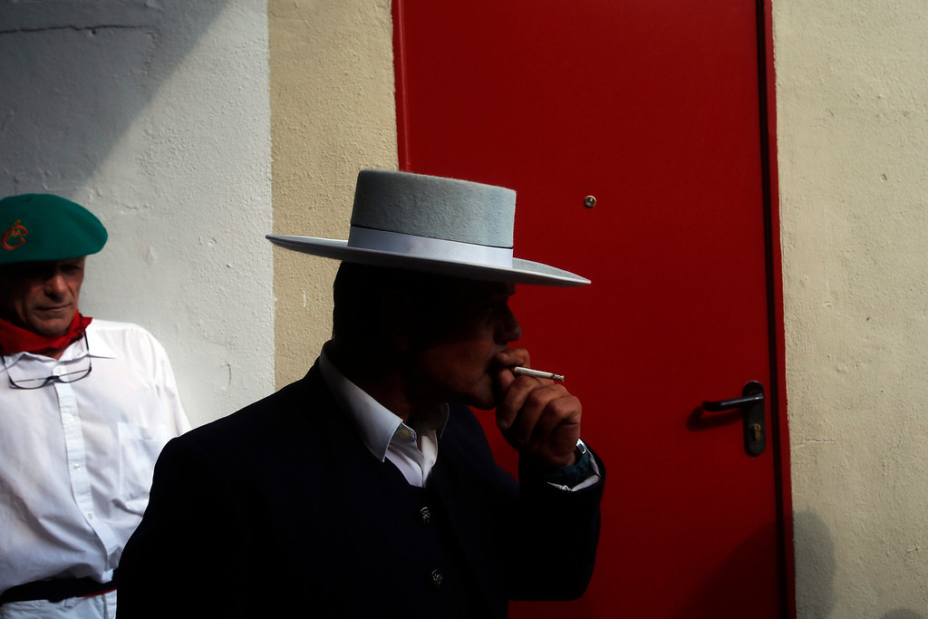 ". The ""mayoral\"" (head of the bull herders) smokes a cigarette before the fifth bullfight of the San Fermin festival in Pamplona July 11, 2013. REUTERS/Susana Vera"