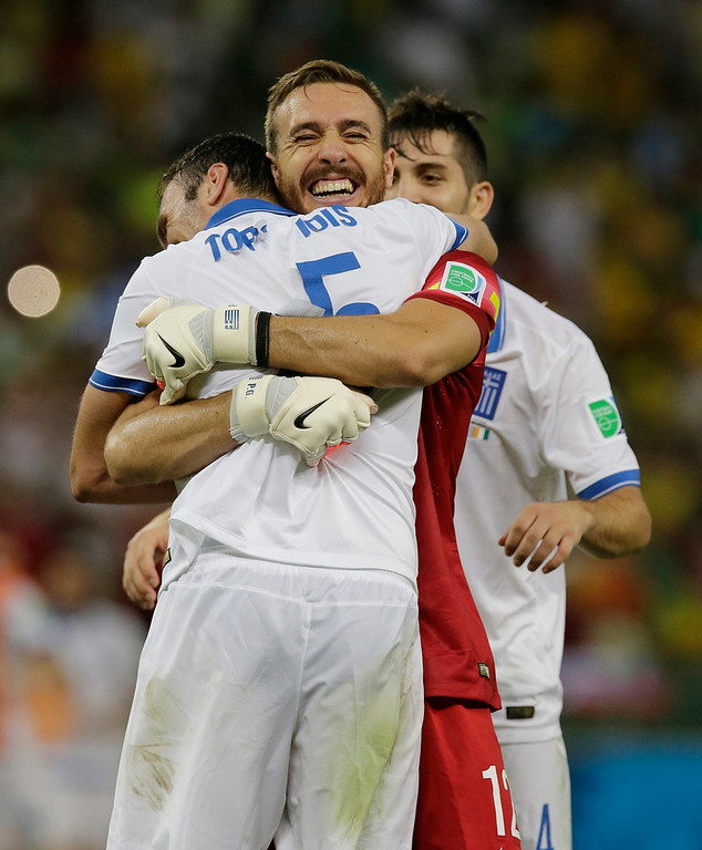 . Greece\'s goalkeeper Panagiotis Glykos celebrates with teammate Vasilis Torosidis after Greece\'s 2-1 victory over Ivory Coast during the group C World Cup soccer match between Greece and Ivory Coast at the Arena Castelao in Fortaleza, Brazil, Tuesday, June 24, 2014. (AP Photo/Bernat Armangue)