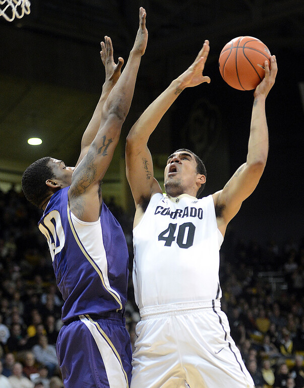 . Josh Scott of Colorado shoots over Shawn Kemp of Washington during the first half of an NCAA college basketball game in Boulder, Colo., Sunday, Feb. 9, 2014. (AP Photo/Daily Camera, Cliff Grassmick)