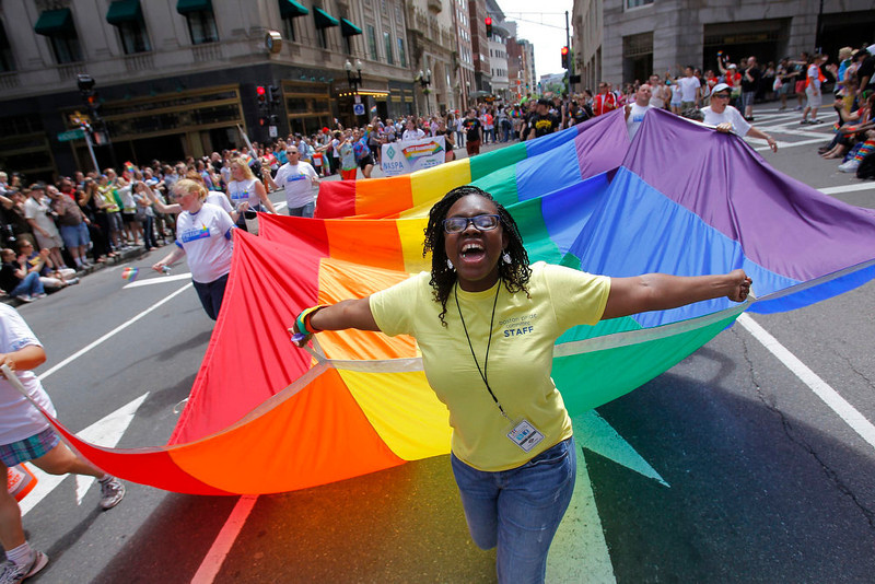 . Jaiy Dickson of Boston helps carry a rainbow flag as she marches during the Gay Pride Parade in Boston, Massachusetts June 8, 2013. REUTERS/Jessica Rinaldi