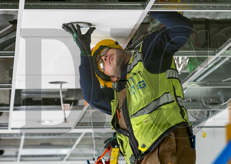 Journeyman electrician Charlie Niemann, a member of Local 48 and an employee of Oregon Electric Group, installs a ceiling light fixture at the Wells Fargo Center. (Josh Kulla/DJC)