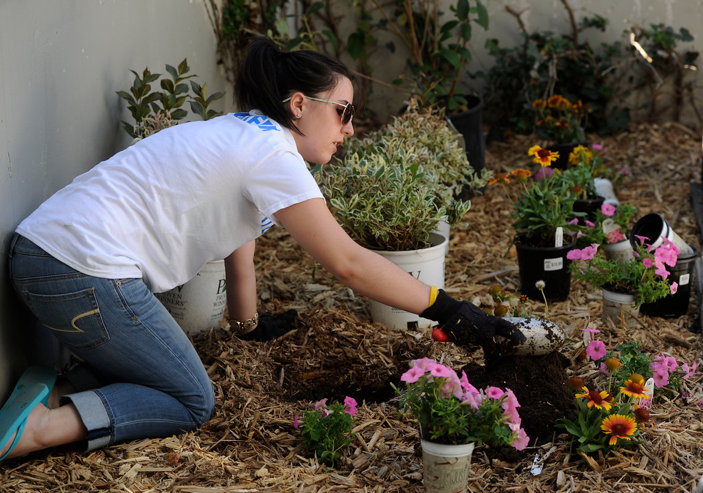 . AURORA, CO - JULY 20:  Volunteer, Theresa Droege, prepares a flower garden as part of volunteer service projects associated with the 7/20 Day of Remembrance 2013 at the Aurora Strong Resilience Center in Aurora Saturday morning, July 20, 2013. Over 200 people attended an earlier service at the Aurora Municipal Center service in honor of the 12 people killed and over 60 people injured in last years Aurora theater shooting. The memorial service, marking the one-year anniversary of the tragic shooting,  included prayer, songs and speeches from local officials and the Governor of Colorado, John Hickenlooper. (Photo By Andy Cross/The Denver Post)