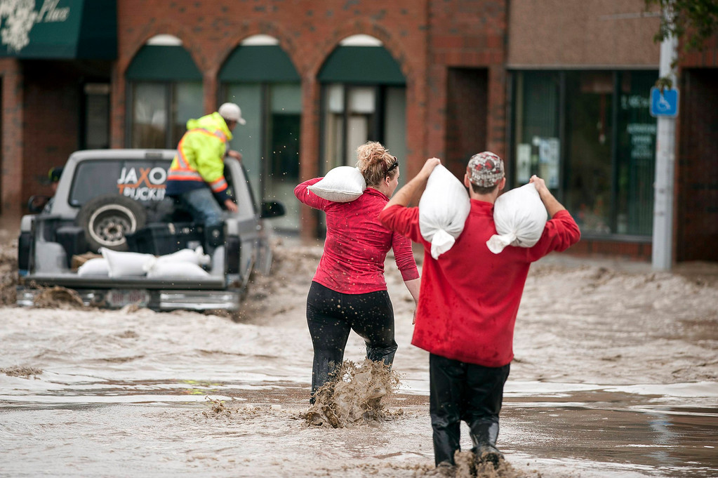 . Residents carrying sandbags wade through floodwater in High River in Alberta province June 20, 2013. A state of emergency has been issued for the town of High River, which is being evacuated due to floods. REUTERS/Mike Sturk