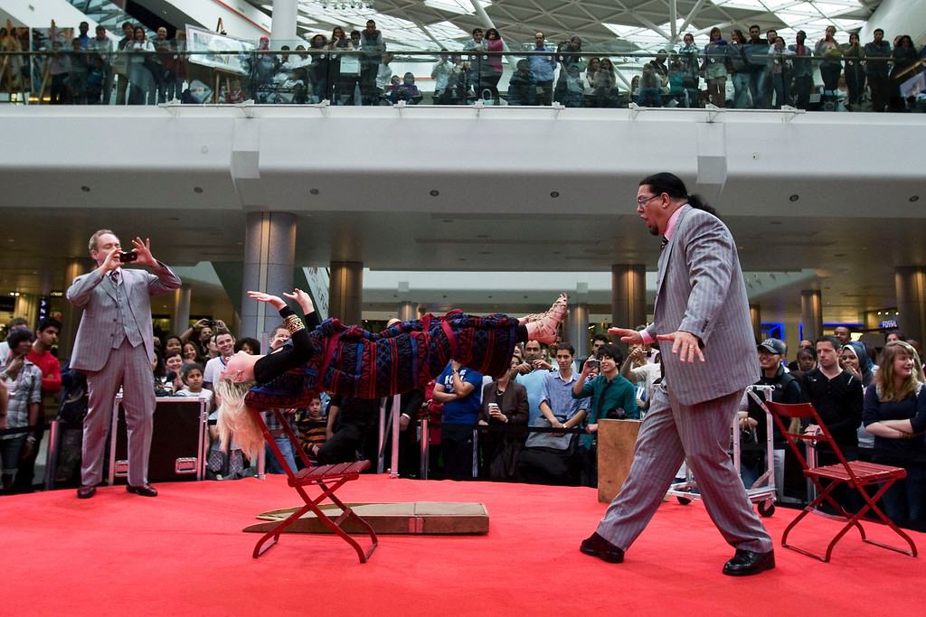 . U.S. illusionists and magicians Penn Jillette, right, and Raymond Teller perform a trick on a member of the public at Westfield Shopping centre in London to promote their 5 night Penn & Teller shows, starting Wednesday, in London, Tuesday, July 13, 2010. (AP Photo/Sang Tan)