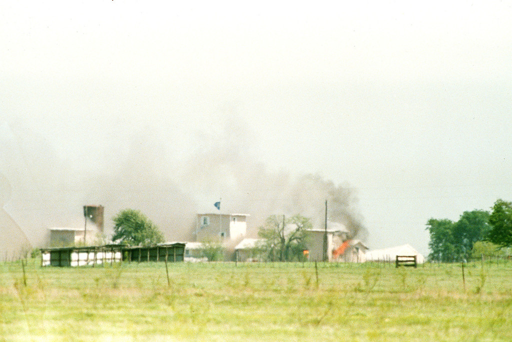 . Flames are seen in building to right of tower and smoke blows into the sky as the fire first becomes visible at the Branch Davidian compound near Waco, Texas, on April 19, 1993. The compound burned to the ground and the Justice Department said cult members set the fire. (AP PHOTO/Roberto Borea)