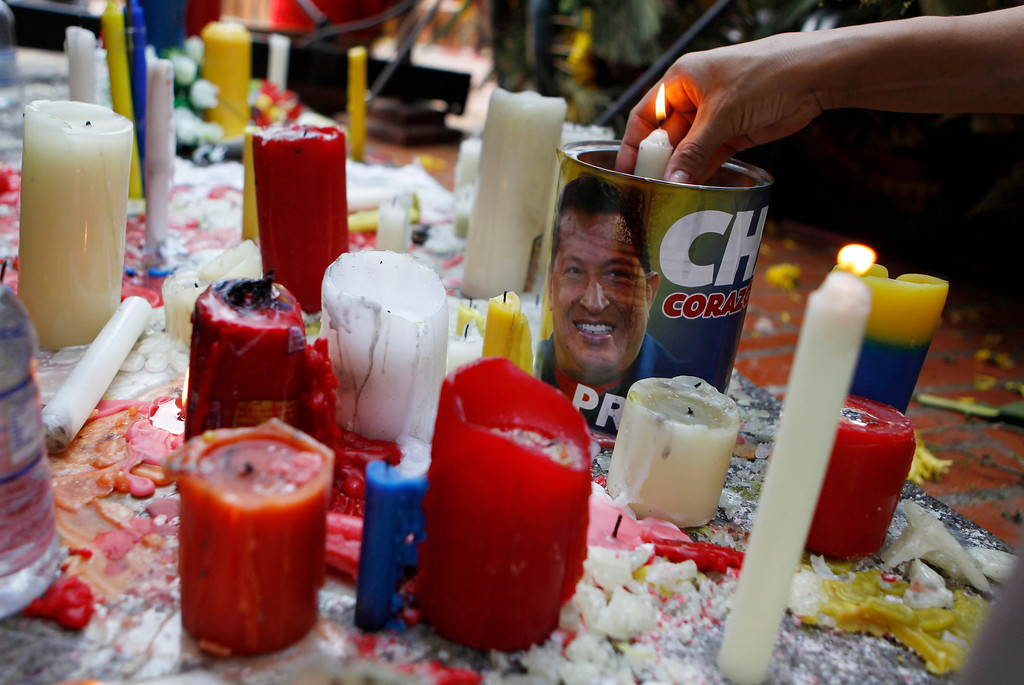 . A woman lights candles during a ceremony for late President Hugo Chavez at the Bolivar square in Barinas, the capital of the state where he was born in western Venezuela, Friday, March 8, 2013.  (AP Photo/Esteban Felix)