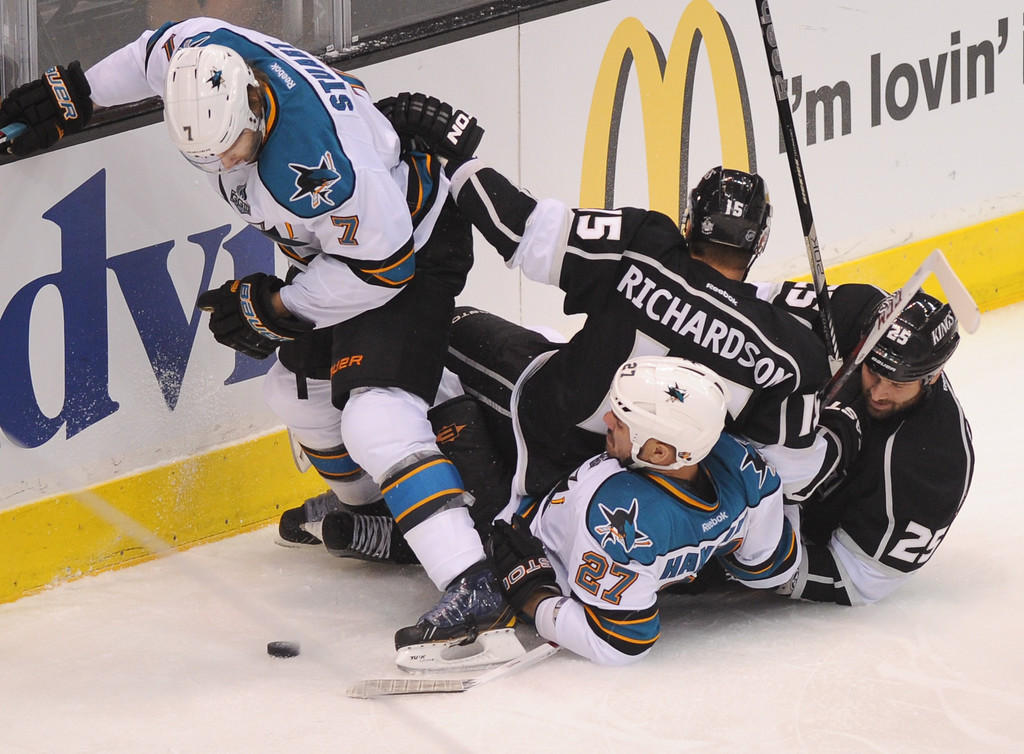 . Kings Brad Richardson (#15) and Dustin Penner (#25) tumble atop the Sharks\'s Scott Hannan as Brad Stuart, left, looks for the puck in game two of the second round of playoffs, Thursday, May 16, 2013, at Staples Center. (Michael Owen Baker/Staff Photographer)