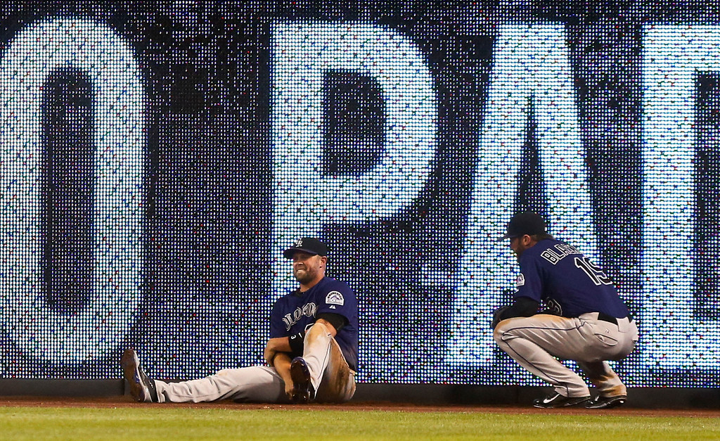 . Colorado Rockies right fielder Michael Cuddyer holds his arm as teammate Charlie Blackmon squats next to him after Cuddyer crashed in the wall trying to make a catch in the fifth inning of a baseball game Monday, April 14, 2014, in San Diego. Cuddyer left the game. (AP Photo/Lenny Ignelzi)
