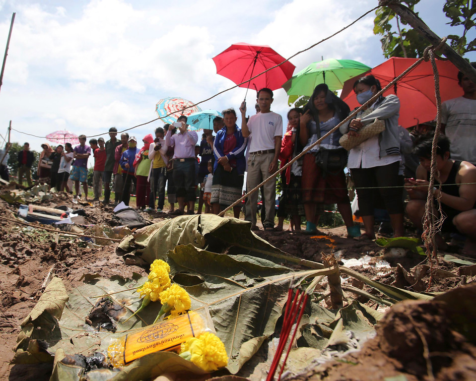 . People look at the debris of a Lao Airlines turboprop plane that crashed, in Pakse, Laos on Thursday, Oct. 17, 2013.  (AP Photo/Sakchai Lalit)