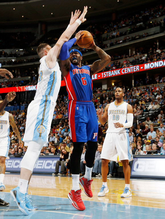 . Detroit Pistons forward Josh Smith, center, drives lane for shot as Denver Nuggets center Jusuf Nurkic, left, of Bosnia Herzegovina, and guard Arron Afflalo cover in the first quarter of an NBA basketball game in Denver on Wednesday, Oct. 29, 2014. (AP Photo/David Zalubowski)