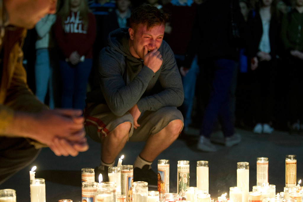 . A mourner cries after placing a candle at a vigil for six Irish students Wednesday, June 17, 2015, in Berkeley, Calif. The six Irish students died when a balcony collapsed during a party.  (AP Photo/Beck Diefenbach)