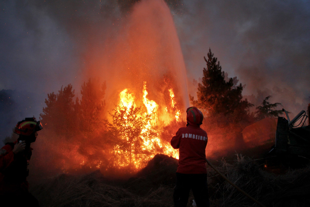 . Portuguese firefighters work to extinguish a wildfire near Caramulo, north Portugal, Thursday, Aug. 29, 2013. Portuguese officials said a woman firefighter died in a forest blaze, becoming the fifth fatality among emergency crews in a month as summer wildfires scorch large areas of parched countryside. (AP Photo/Francisco Seco)