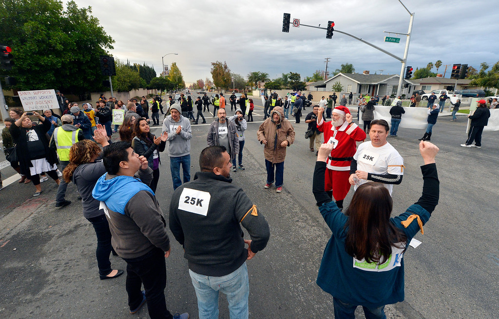 . Ten Walmart protesters were read their rights before being arrested for failure to disperse after sitting down in the middle of the intersection at 5th and Mountain Avenues in Ontario Friday morning November 29, 2013. Over 100 protesters came to the Walmart on Mountain Avenue to protest against Walmart\'s wages and benefits.   (Will Lester/Inland Valley Daily Bulletin)