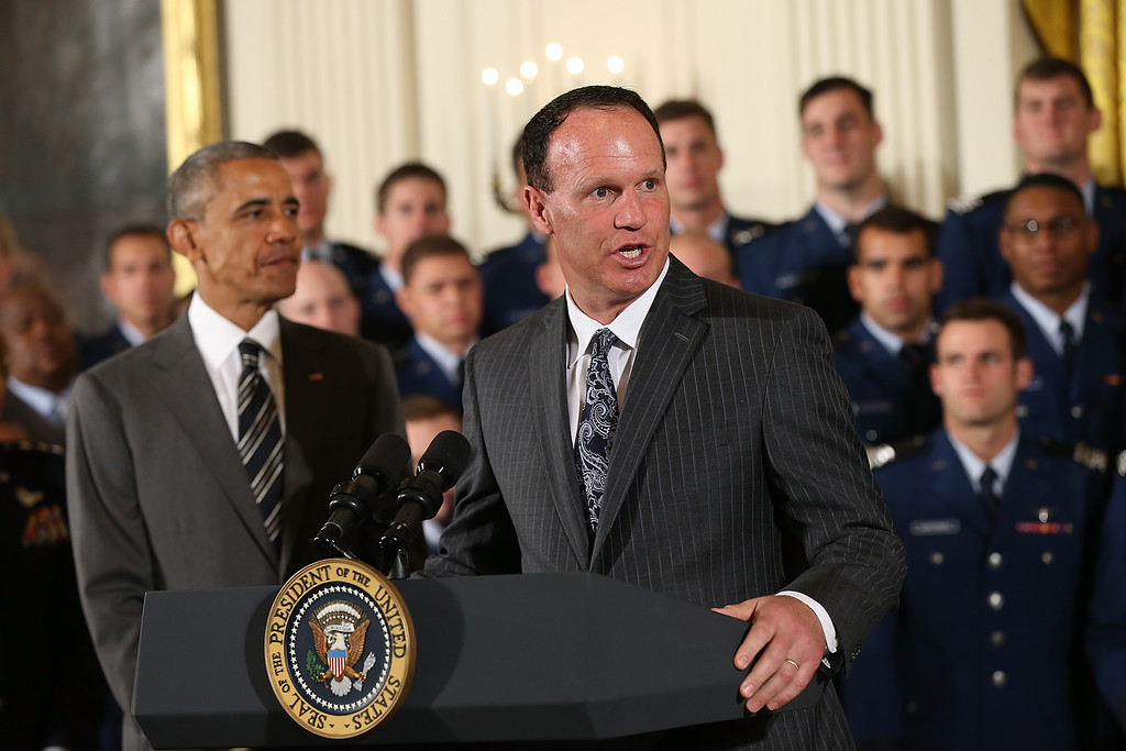. Air Force head football coach Troy Calhoun (R) speaks as U.S. President Barack Obama (L) listens during the Commander-in-Chief trophy presentation to the United States Air Force Academy football team in the East Room of the White House May 7, 2015 in Washington, DC. The Commander-in-Chief trophy is awarded each year to the winner of the American football series featuring the U.S. Naval Academy, U.S. Air Force Academy and U.S. Military Academy. (Photo by Win McNamee/Getty Images)