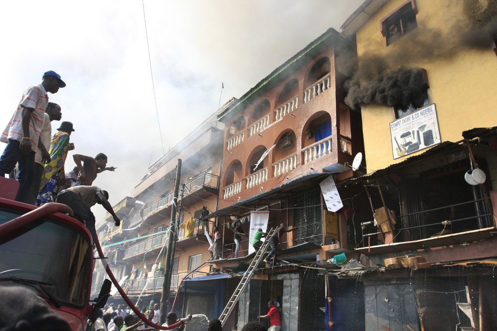 Description of . A group of men try to direct firefighting efforts at a burning city block on Lagos Island in Lagos, Nigeria, on Wednesday, Dec. 26, 2012. An explosion ripped through a warehouse Wednesday where witnesses say fireworks were  stored in Nigeria's largest city, sparking a fire. It wasn't immediately clear if anyone was injured in the blast that firefighters and locals struggled to contain. (AP Photo/Jon Gambrell)