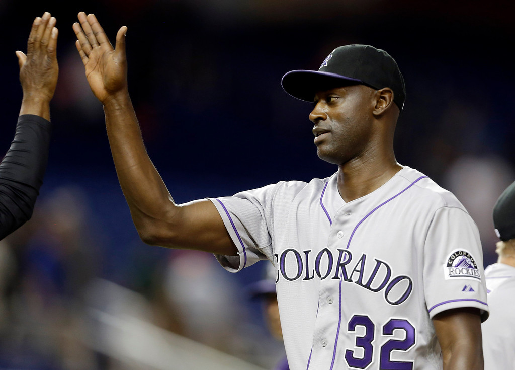 . Colorado Rockies relief pitcher LaTroy Hawkins (32) high-fives a teammate after they defeated the Miami Marlins 6-5 in a baseball game on Wednesday, April 2, 2014, in Miami. (AP Photo/Lynne Sladky)