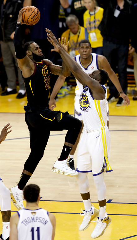 . Cleveland Cavaliers forward LeBron James, left, shoots over Golden State Warriors forward Draymond Green during the second half of Game 1 of basketball\'s NBA Finals in Oakland, Calif., Thursday, May 31, 2018. (AP Photo/Marcio Jose Sanchez)
