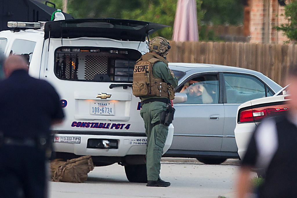 . Law enforcement officers surround a shooting suspect in his car Wednesday, July 9, 2014, in Spring, Texas. Deputies cornered the suspect in a shooting at a suburban Houston home that resulted in multiple fatalities. (AP Photo/Houston Chronicle, Brett Coomer)