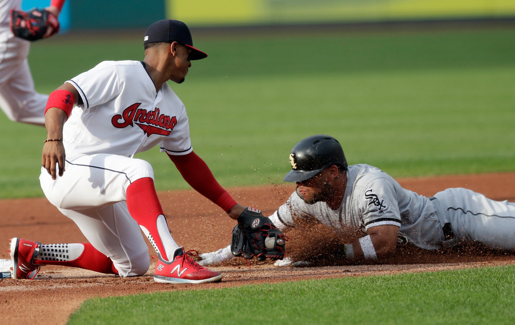 . Cleveland Indians\' Francisco Lindor, left, tags out Chicago White Sox\'s Yoan Moncada after Moncada tried to steal second base in the first inning of a baseball game, Monday, June 18, 2018, in Cleveland. (AP Photo/Tony Dejak)