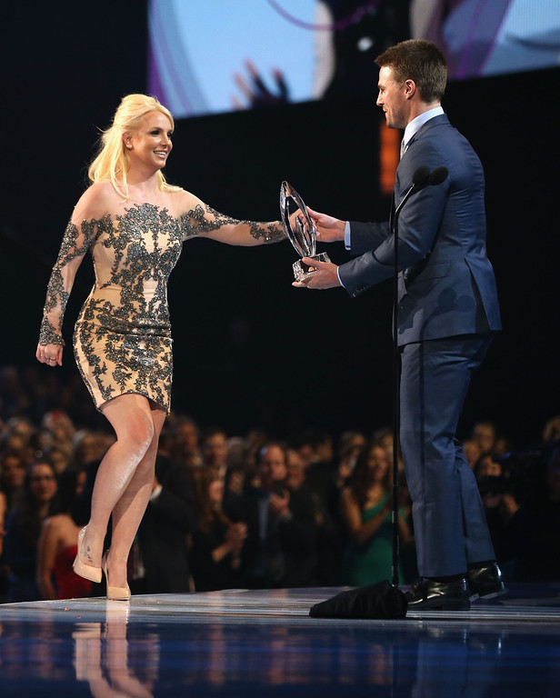 . LOS ANGELES, CA - JANUARY 08:  Singer Britney Spears accepts the Favorite Pop Artist award from actor Stephen Amell onstage at The 40th Annual People\'s Choice Awards at Nokia Theatre L.A. Live on January 8, 2014 in Los Angeles, California.  (Photo by Christopher Polk/Getty Images for The People\'s Choice Awards)