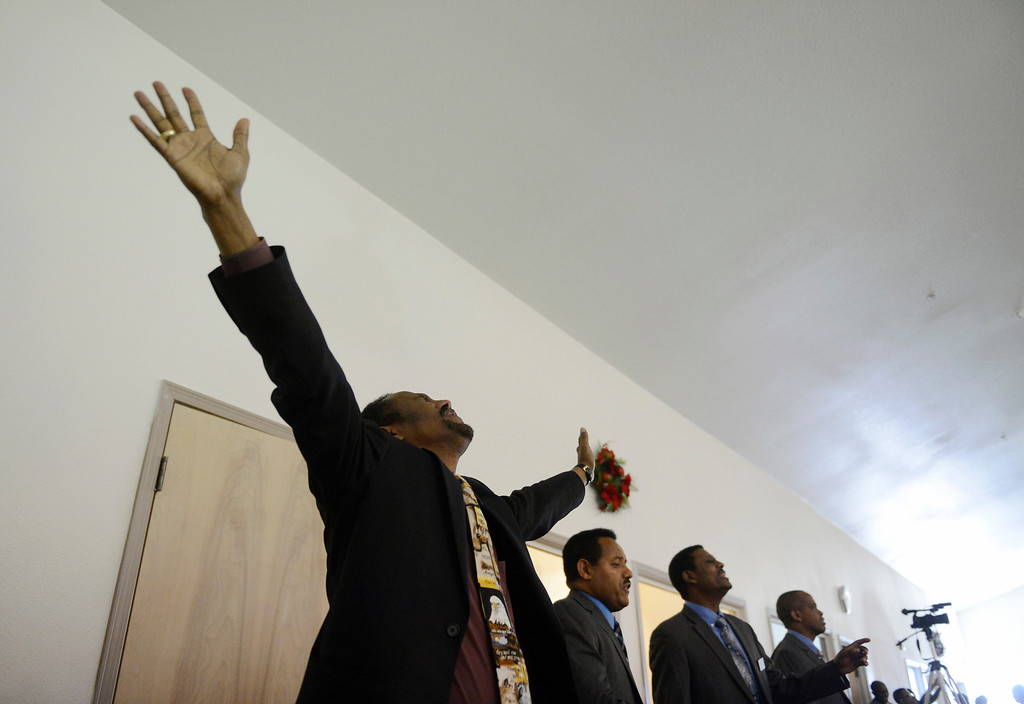 . AURORA, CO. - JANUARY 11:  Addis Kidan Evangelical Church worshipper, Nigusie Assefa Negash, left, celebrates during a song at the church dedication, Saturday, January 10, 2014. (Photo By Andy Cross / The Denver Post)