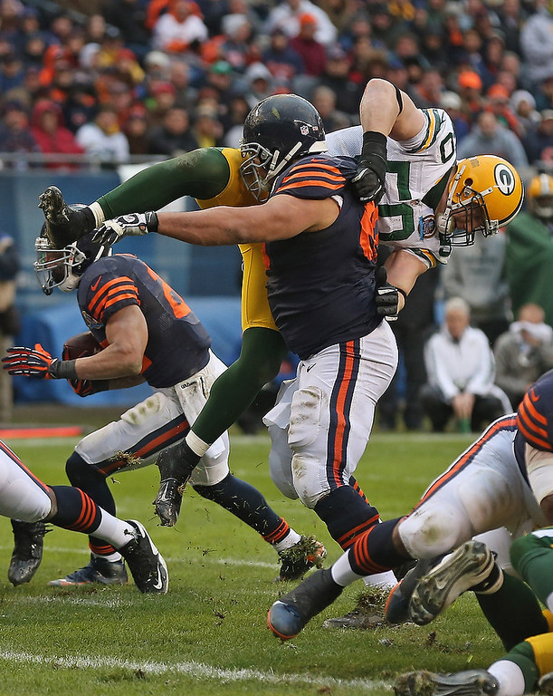 . Roberto Garza #63 of the Chicago Bears flips A.J. Hawk #50 of the Green Bay Packers at Soldier Field on December 16, 2012 in Chicago, Illinois. The Packers defeated the Bears 21-13. (Photo by Jonathan Daniel/Getty Images)